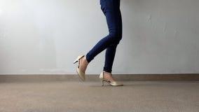 Jambes de femme dans le support d'or de sandales de talon haut sur la terre, fond extérieur Photo stock