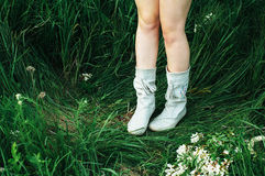Jambes de femme dans les bottes blanches sur l'herbe verte Pieds femelles dans des chaussures photographie stock libre de droits