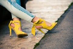 Jambes de femme en sandales jaunes en cuir de talon haut extérieures dans la ville image stock