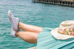 Jambes de femme en surface sur un dock Photographie stock libre de droits