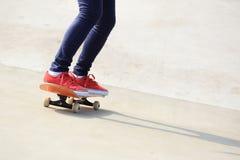 Jambes de femme faisant de la planche à roulettes Images stock