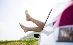 Jambes de femme les fenêtres dans la voiture Photographie stock libre de droits