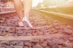 Jambes de femme marchant dans le chemin de fer photo stock