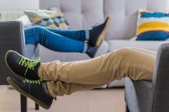 Jambes de femme se reposant sur l'accoudoir de divan Image stock