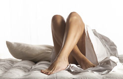 Jambes de femme sur le lit Photographie stock libre de droits