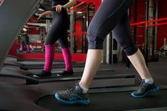 Jambes de femmes dans des espadrilles sur le tapis roulant Photo stock