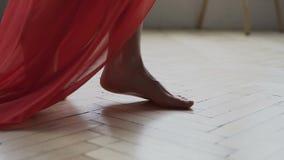 Jambes de fille caucasienne portant la longue robe rouge marchant nu-pieds sur le plancher dans la chambre, Appareil-photo de pas banque de vidéos
