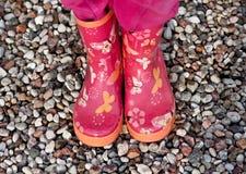 Jambes de fille d'enfant en couvre-chaussures roses sur la plage en pierre Photo libre de droits