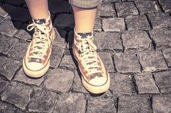 Jambes de fille dans des chaussures en caoutchouc sur le trottoir Photo libre de droits