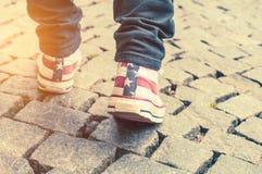 Jambes de fille dans des chaussures en caoutchouc sur le trottoir Photographie stock