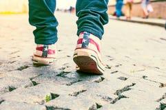 Jambes de fille dans des espadrilles sur le trottoir Photo stock