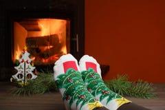 Jambes de fille dans les chaussettes près de la cheminée avec un peu d'arbre de Noël Photo stock
