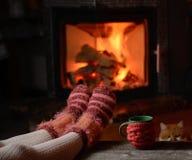 Jambes de fille dans les chaussettes près de la cheminée avec une tasse Images stock