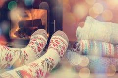 Jambes de fille dans les chaussettes tricotées près de la cheminée avec une pile de c Photo libre de droits