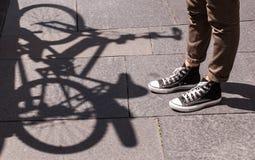 Jambes de fille utilisant des ricanements de noir et des pantalons bruns maigres devant l'ombre d'une bicyclette Images libres de droits