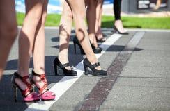 Jambes de filles dans des talons hauts sur la grille commençante Images libres de droits