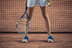 Jambes de Fmale avec la raquette et la boule de tennis Images stock