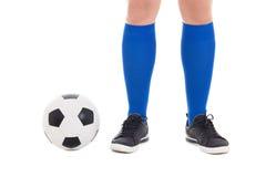 Jambes de footballeur dans les chaussettes bleues avec la boule d'isolement sur le blanc Photos stock