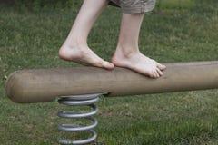 Jambes de garçon sur un faisceau d'équilibre Avancez Étapes de succès image libre de droits
