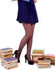 Jambes de jeune femme avec des livres d'isolement sur le blanc photo libre de droits