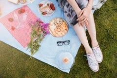 Jambes de jeune femme se reposant sur la couverture et ayant le pique-nique Photos stock