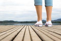 Jambes de jeune fille avec les chaussures et les blues-jean blanches sur un pilier en bois Image libre de droits