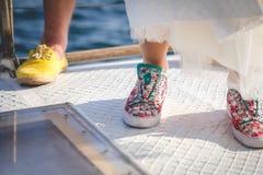 Jambes de jeune mariée et de groom dans des chaussures de couleur Photographie stock