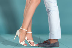 Jambes de jeunes couples contre le mur blanc Photographie stock libre de droits