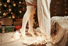 Jambes de jeunes couples dans l'intérieur en bois foncé avec des lumières, lanterne de bougie Étreindre d'homme et de femme Vacan Images libres de droits