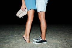 Jambes de jeunes couples se tenant sur la plage la nuit Photographie stock libre de droits