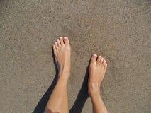 Jambes de jeunes femmes se tenant sur le sable sur la plage photographie stock libre de droits