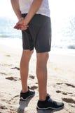 Jambes de l'homme en bref et des espadrilles se tenant sur la plage Photos libres de droits