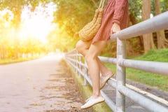 Jambes de la fille asiatique adolescente seul s'asseyant sur la barrière le jour d'été Images stock