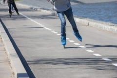 Jambes de la fille ayant l'exercice de patin de rouleau le long de l'alignement de routes image stock