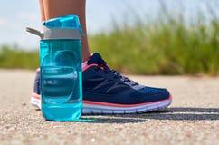Jambes de la fille dans des espadrilles Les sports mettent en bouteille avec de l'eau Photographie stock libre de droits