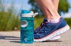 Jambes de la fille dans des espadrilles Les sports mettent en bouteille avec de l'eau Image libre de droits