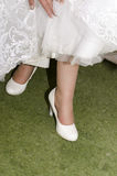 Jambes de la jeune mariée dans les chaussures et des robes blanches de bord sur l'herbe verte Image stock