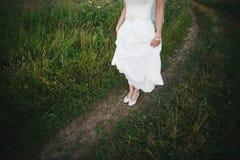 Jambes de la jeune mariée sur la nature Image stock