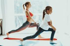 Jambes de maman et de fille s'étendant à la formation de yoga images stock
