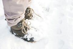 Jambes de personne tenant la neige avec les bottes et le pantalon isolé Image libre de droits