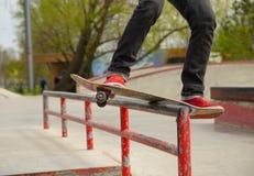 Jambes de planchiste dans les sneackers montant la planche à roulettes au skatepark, faisant le tour photographie stock