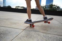 Jambes de planchiste de femme faisant de la planche à roulettes Photographie stock