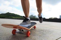 Jambes de planchiste de femme faisant de la planche à roulettes Image stock
