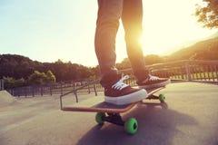 Jambes de planchiste faisant de la planche à roulettes au parc de patin Images libres de droits