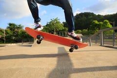 Jambes de planchiste faisant de la planche à roulettes au skatepark Image libre de droits