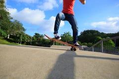 Jambes de planchiste faisant de la planche à roulettes au skatepark Photographie stock libre de droits