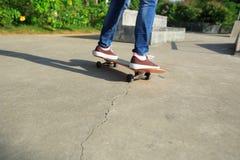 Jambes de planchiste faisant de la planche à roulettes au skatepark Photo libre de droits