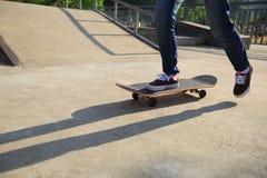 Jambes de planchiste faisant de la planche à roulettes au skatepark Image stock