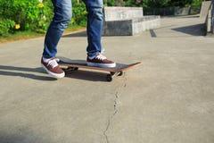 Jambes de planchiste faisant de la planche à roulettes au skatepark Photos libres de droits
