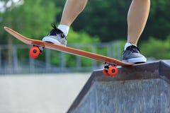 Jambes de planchiste faisant de la planche à roulettes au skatepark Images libres de droits